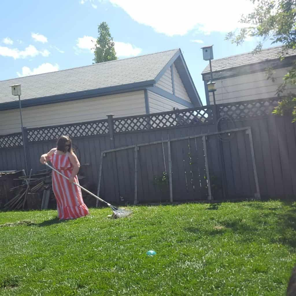 Leah Johns raking the lawn in a dress during June Dresses